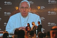 Pope Francis, who spoke of the importance of education and teachers in a video message to the audience, introduces the winner of the second annual Global Teacher Prize, Palestinian primary school teacher Hanan al-Hroub, who receives her trophy from Sheikh Mohammed Bin Rashid Al Maktoum, UAE Vice President and the Ruler of Dubai, center, in Dubai, United Arab Emirates, Sunday, March 13, 2016. Al-Hroub who encourages students to renounce violence won a $1 million prize for teaching excellence. (AP Photo/Kamran Jebreili)
