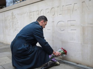 LONDON, ENGLAND - MARCH 23: A man lays flowers outside New Scotland Yard following yesterday's attack in which one police officer was killed on March 23, 2017 in London, England. Four people have been killed and around 40 people injured following yesterday's attack by the Houses of Parliament in Westminster.