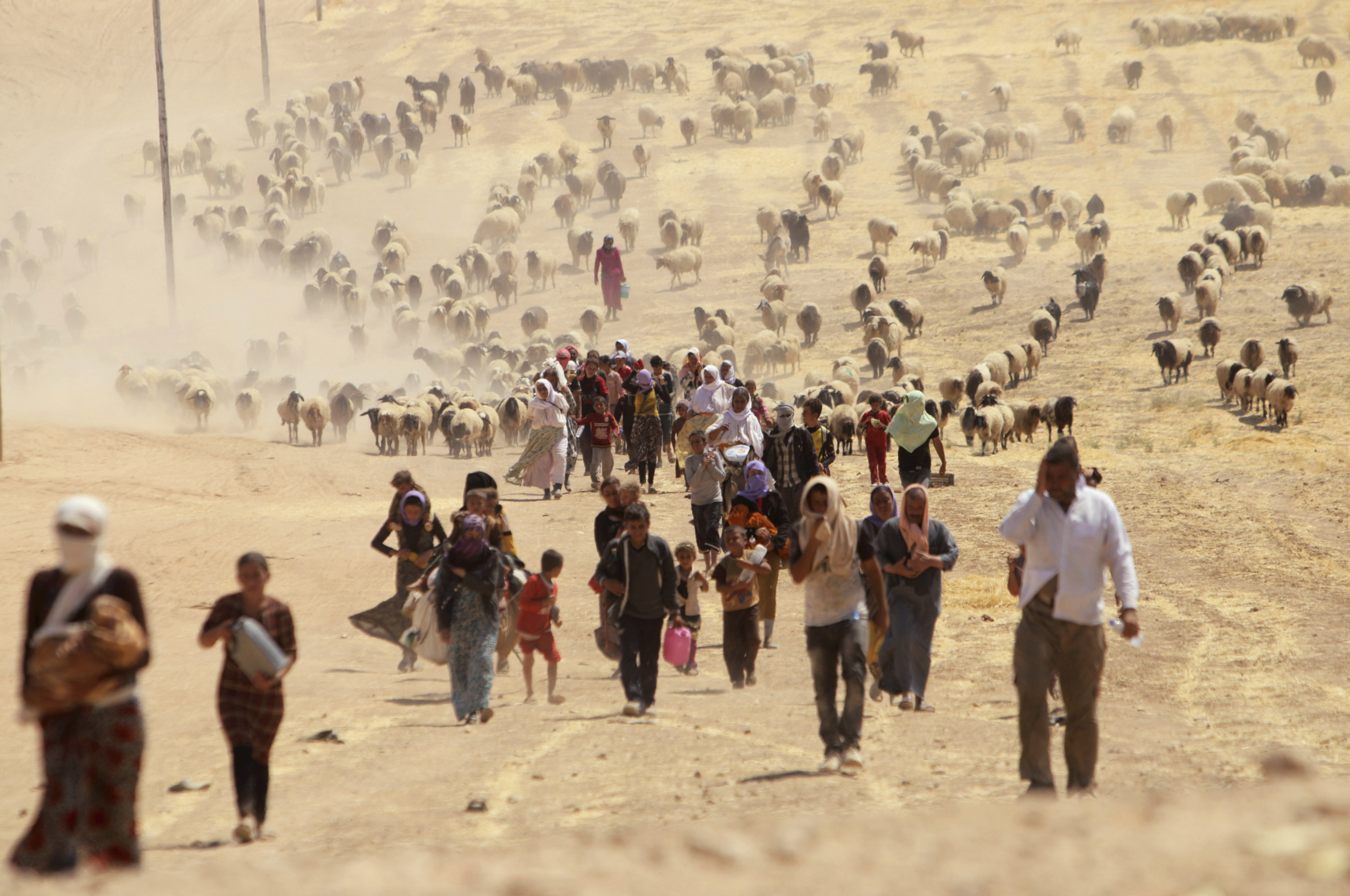 Displaced people from the minority Yazidi sect, fleeing violence from forces loyal to the Islamic State in Sinjar town, walk towards the Syrian border, on the outskirts of Sinjar mountain, near the Syrian border town of Elierbeh of Al-Hasakah Governorate August 10, 2014. Islamic State militants have killed at least 500 members of Iraq's Yazidi ethnic minority during their offensive in the north, Iraq's human rights minister told Reuters on Sunday. The Islamic State, which has declared a caliphate in parts of Iraq and Syria, has prompted tens of thousands of Yazidis and Christians to flee for their lives during their push to within a 30-minute drive of the Kurdish regional capital Arbil. Picture taken August 10, 2014. REUTERS/Rodi Said (IRAQ - Tags: POLITICS CIVIL UNREST CONFLICT TPX IMAGES OF THE DAY) - RTR41YW4
