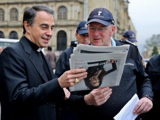 Archbishop Ettore Balestrero, apostolic nuncio to Colombia, and Domenico Giani, Pope Francis' lead bodyguard, look at a newspaper during a May 8 walk through the streets in downtown Bogota. The pope is scheduled to visit four Colombian cities, starting his trip in the Bogota, the capital, Sept. 6, followed by day trips to Villavicencio and Medellin Sept. 8 and 9, and Mass in Cartagena Sept. 10. (CNS photo/Leonardo Munoz, EPA) See COLOMBIA-POPE June 23, 2017.