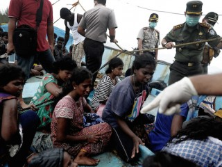 Migrants from Sri Lanka remain on their boat despite their vessel being washed ashore on the west coast of Lhoknga in Aceh Besar, Indonesia's Aceh province on June 14, 2016.  Dozens of Sri Lankan immigrants bound for Australia were stranded off Aceh in northwest Indonesia after their boat broke down, local officials said on June 12. / AFP PHOTO / CHAIDEER MAHYUDDIN