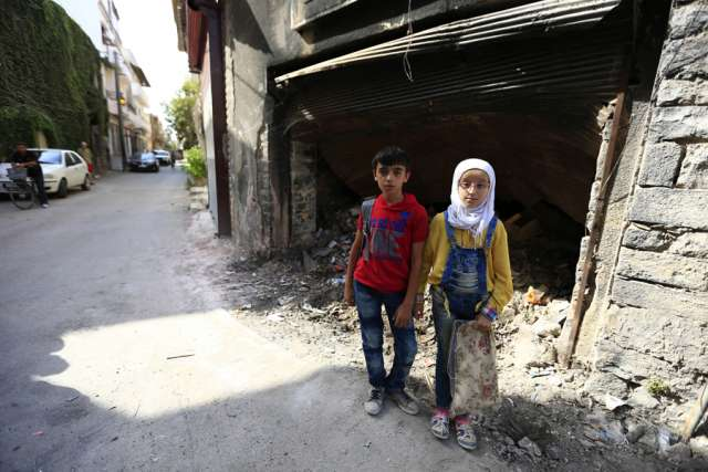 12_year_old_twins_from_the_old_city_of_Homs_stand_near_garbage_outside_a_dilapidated_building_Credit___UNICEF_UNI201161_Ohanesian_CNA_1_13_16