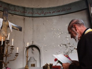 BAGHDAD, IRAQ - OCTOBER 17:  An Iraqi Christian Priest leads a Sunday service at a destroyed Roman Catholic Church October 17, 2004 in Baghdad, Iraq. On Saturday, a series of bombings damaged five churches as part of an escalation in attacking the Christian minority of Baghdad.  (Photo by Marco Di Lauro/Getty Images)