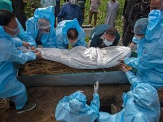 Người thân mặc đồ bảo hộ chôn cất một nạn nhân chết vì Covid-19. (Ảnh: AFP)