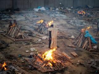 Các thành viên trong gia đình ôm nhau giữa giàn hỏa thiêu các nạn nhân Covid-19 tại một khu hỏa táng ở New Delhi vào ngày 26 tháng 4. (Ảnh: Jewel Samad / AFP)