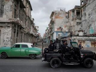 Một chiếc xe của lực lượng đặc biệt đi ngang qua một chiếc xe cổ ở trung tâm thành phố Havana ngày 13 tháng 7 năm 2021. (Nguồn: CNS photo / Alexandre Meneghini, Reuters)
