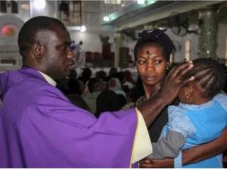 Một linh mục ký tên lên trán một đứa trẻ khi những người theo đạo Công giáo tham gia lễ kỷ niệm Thứ Tư Lễ Tro tại nhà thờ Thánh Patrick ở Maiduguri vào ngày 26 tháng 2 năm 2020. (Ảnh: Audu Marte / AFP / Getty)