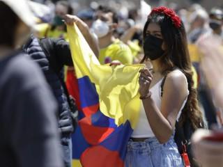 Một phụ nữ cầm cờ Colombia khi tham dự buổi cầu nguyện buổi trưa của Giáo hoàng Francis Angelus tại Quảng trường Thánh Peter ở Vatican, Chủ nhật, ngày 9 tháng 5 năm 2021 (Ảnh: Gregorio Borgia / AP)
