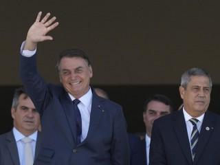 Tổng thống Brazil Jair Bolsonaro sóng sánh bên cạnh Bộ trưởng Quốc phòng Walter Braga Netto khi một đoàn xe quân sự đi qua cung điện tiền nhiệm Planalto ở Brasilia, Brazil, thứ Ba, ngày 10 tháng 8 năm 2021. Đoàn xe diễu hành qua cung điện vào thứ Ba, ngày diễn ra cuộc bỏ phiếu quan trọng của quốc hội về một đề xuất cải cách hiến pháp được Bolsonaro hỗ trợ sẽ thêm biên lai in vào một số thùng phiếu điện tử của quốc gia. (Nguồn: Eraldo Peres / A)